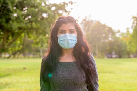 Young Indian woman with mask for protection from corona virus outbreak at the park