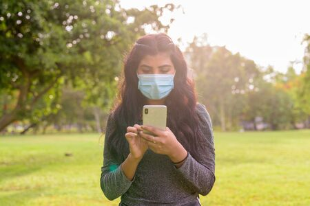 Young Indian woman with mask using phone at the park 写真素材