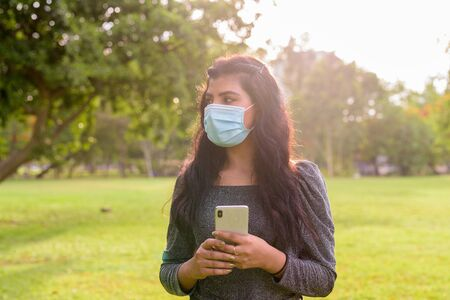 Young Indian woman with mask thinking while using phone at the park