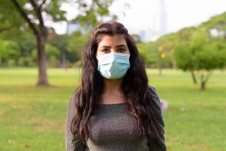 Face of young Indian woman with mask relaxing at the park
