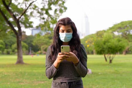 Young Indian woman with mask using phone while relaxing at the park