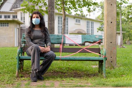 Young Indian woman with mask thinking while sitting with distance on park bench