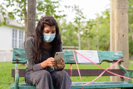 Young Indian woman with mask using phone while sitting with distance on park bench
