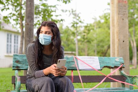 Young Indian woman with mask thinking and using phone while sitting with distance on park bench