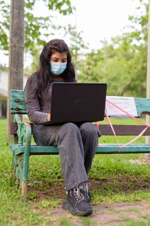 Young Indian woman with mask using laptop while sitting with distance on park bench