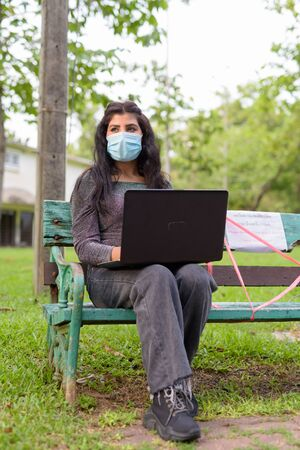 Young Indian woman with mask thinking and using laptop while sitting with distance on park bench