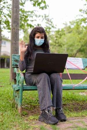 Young Indian woman with mask video calling while sitting with distance on park bench 写真素材