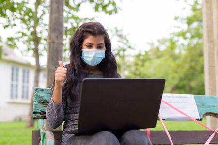 Young Indian woman with mask video calling and giving thumbs up while sitting with distance on park bench