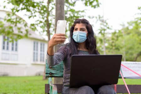 Young Indian woman with mask video calling using phone while sitting with distance on park bench