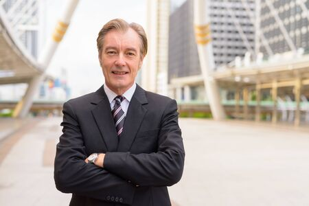 Happy mature handsome businessman smiling with arms crossed at the skywalk bridge Фото со стока