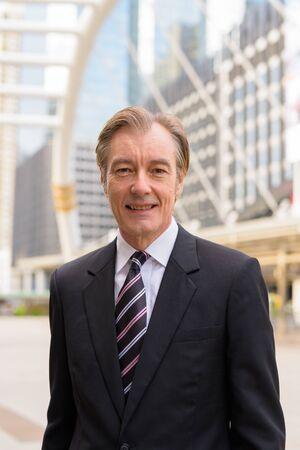 Happy mature handsome businessman in suit smiling at skywalk bridge in the city Foto de archivo
