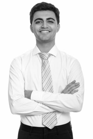 Portrait of happy young handsome Persian businessman smiling with arms crossed Foto de archivo