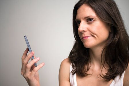 Face of beautiful woman thinking while using phone