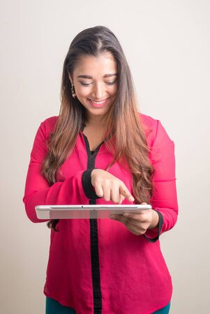 Portrait of happy young beautiful Indian businesswoman using digital tablet