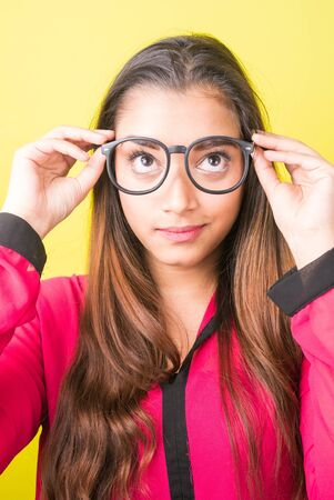 Face of young beautiful Indian businesswoman with eyeglasses