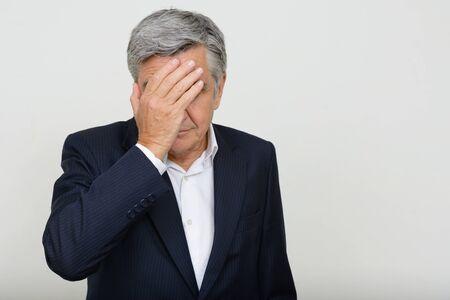 Portrait of stressed senior businessman in suit showing face palm gesture