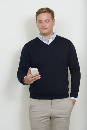 Portrait of man with blond hair using phone