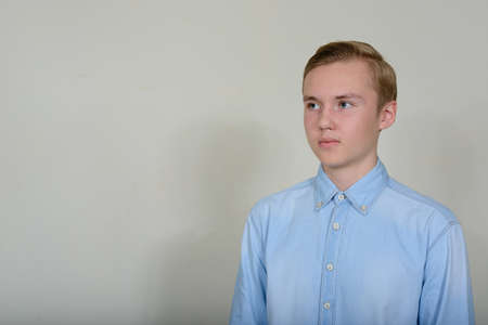 Portrait of young handsome blond teenage boy thinking