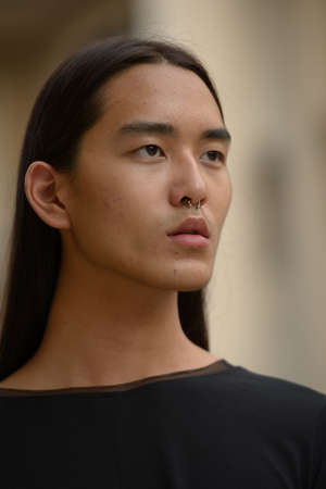 Face of young Asian man with long hair thinking in the city