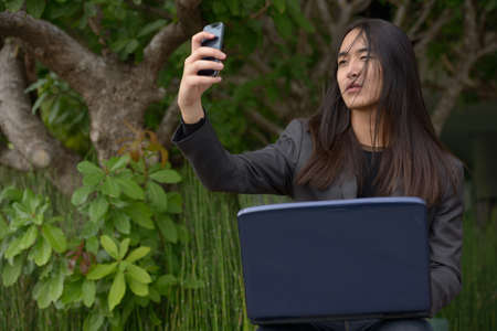 Young Asian businessman with long hair taking selfie at the park