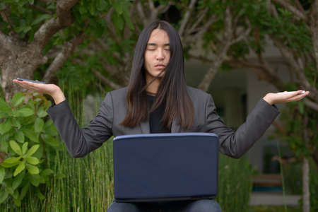 Young Asian businessman with long hair holding two phones and laptop while meditating at the park