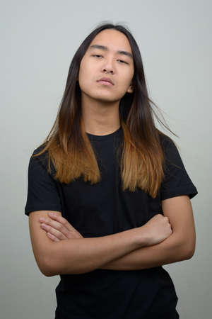 Young Asian man with long hair with arms crossed