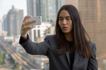 Young Asian businessman with long hair taking selfie in the city outdoors