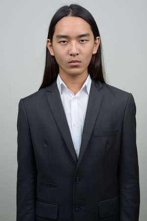 Young Asian businessman with long hair in suit 免版税图像