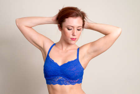 Portrait of beautiful redhead woman wearing underwear with hands behind head