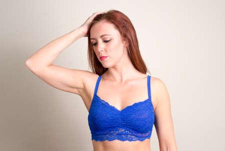 Portrait of beautiful redhead woman wearing underwear with hand behind head