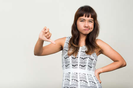 Portrait of stressed young Asian woman giving thumbs down Stockfoto