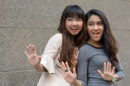 Two happy young Asian businesswomen together in the city Stockfoto