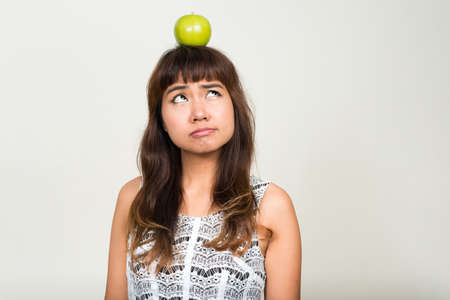 Portrait of young beautiful Asian woman with apple on top of head