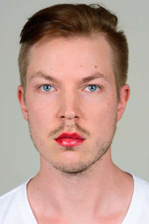 Portrait of young man with beard stubble wearing makeup Stock Photo