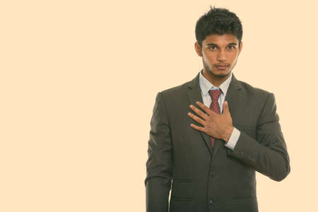 Studio shot of young handsome Indian businessman with hand on chest