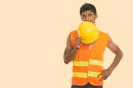 Young handsome Indian man construction worker covering face with safety helmet while thinking