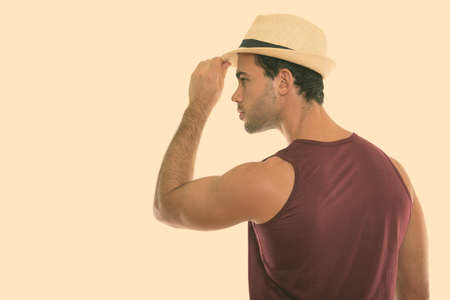 Profile view of young handsome Hispanic man holding hat Imagens