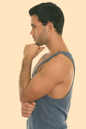 Profile view of young handsome Hispanic man thinking