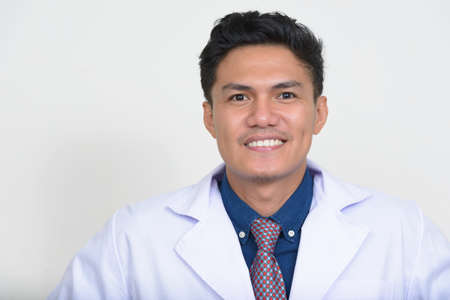 Portrait of happy handsome Asian man doctor smiling