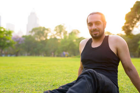 Happy young handsome bearded Indian man sitting at the park