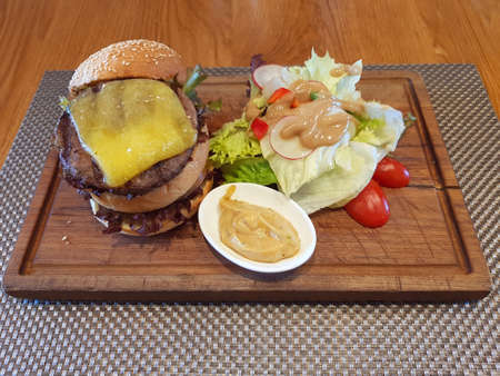 Double Cheeseburger Served On Wooden Plate At Restaurant Zdjęcie Seryjne