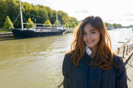Young happy Asian woman standing in pier with vintage black boat in the river