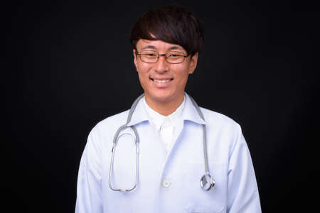 Young handsome Asian man doctor against black background