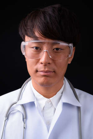 Young handsome Asian man doctor wearing protective glasses against black background 免版税图像