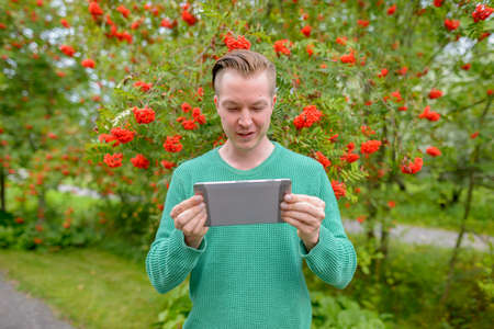 Portrait of young handsome blond man with digital tablet outdoors