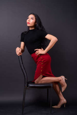 Young beautiful Asian transgender businesswoman against black background