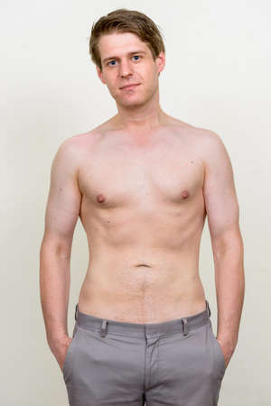 Portrait of young handsome shirtless man looking at camera