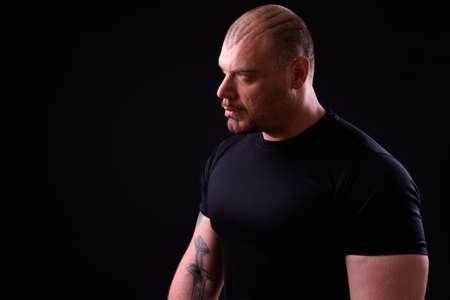 Portrait of muscular bald man against black background 스톡 콘텐츠