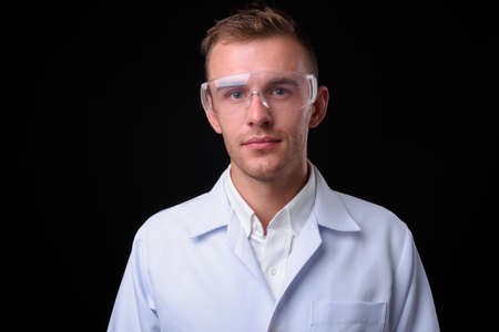Portrait of young handsome man doctor as scientist with protective glasses
