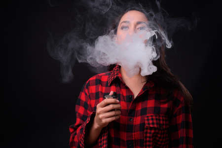 Young beautiful Asian woman vaping against black background